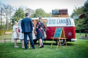 huwelijksgasten wachten voor de VW-combi om een foto van zichzelf te nemen in de VW-combi van foto lama