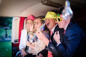 Vier mensen nemen foto's van henzelf met accessoires in de VW combi van foto lama