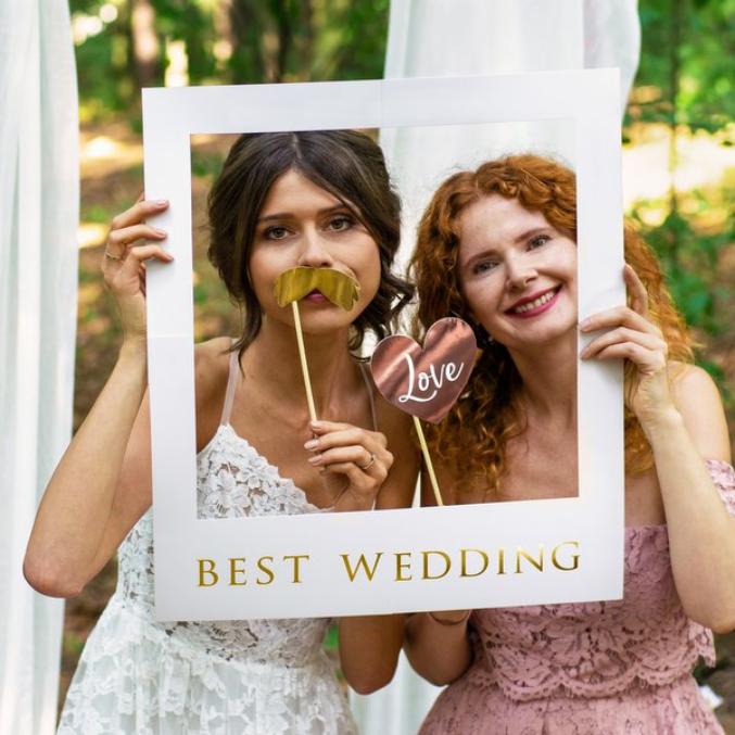 foto van twee vrouwen die foto's van zichzelf nemen met accessoires tijdens een trouwfeest